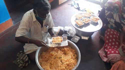 Un homme prépare des rations de riz